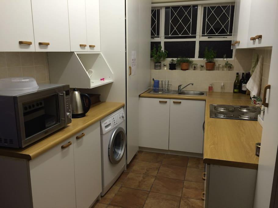 Kitchen with stove/oven, microwave, fridge & washing machine