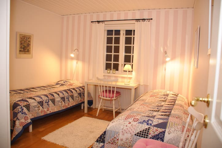 Rosa-sovrummet, det nedre sovrummet med två sängar och rikligt med garderober utmed ena väggen.