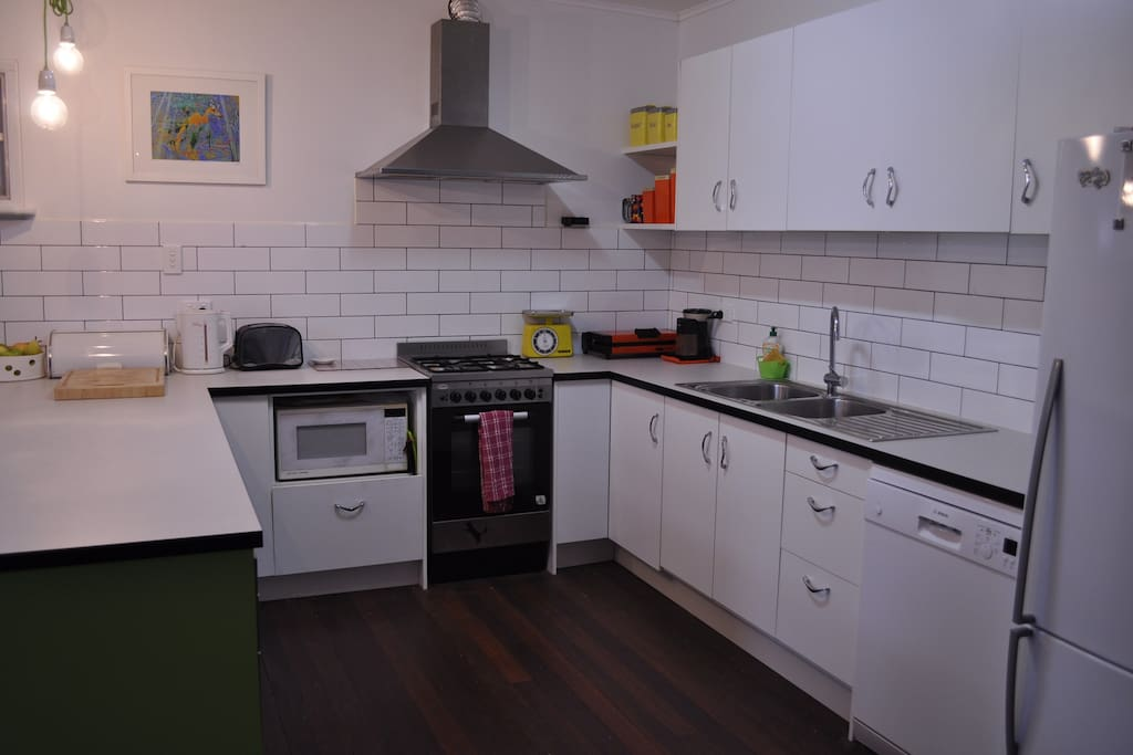 Modern kitchen with gas/electric oven, wine fridge, dishwasher and stocked pantry