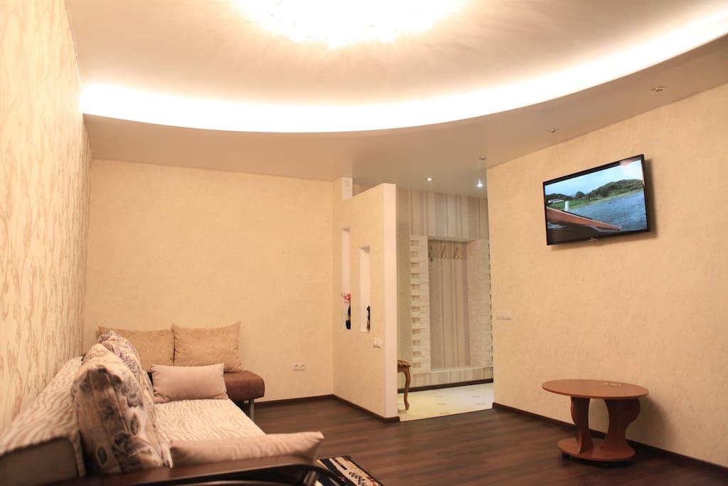 В гостиной установлен диван, тахта, большой ЖКТВ, журнальный столик, обеденный стол