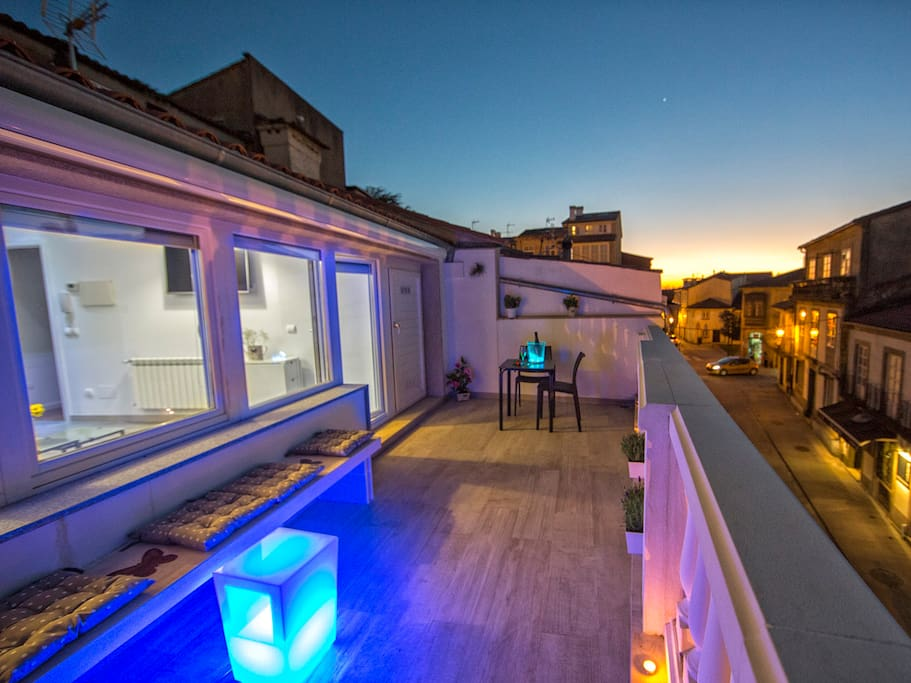 Terraza con banco, mesas con silla y toldo para el sol