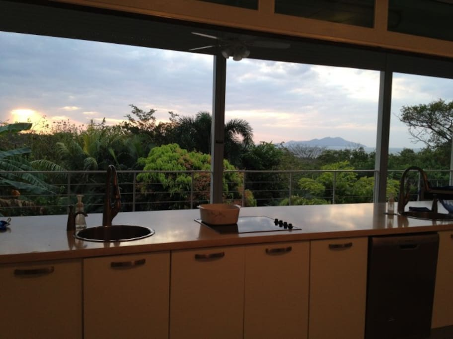 Sunrise from the open kitchen overlooking the terrace and backyard, view view of the ocean and the island farther beyond.