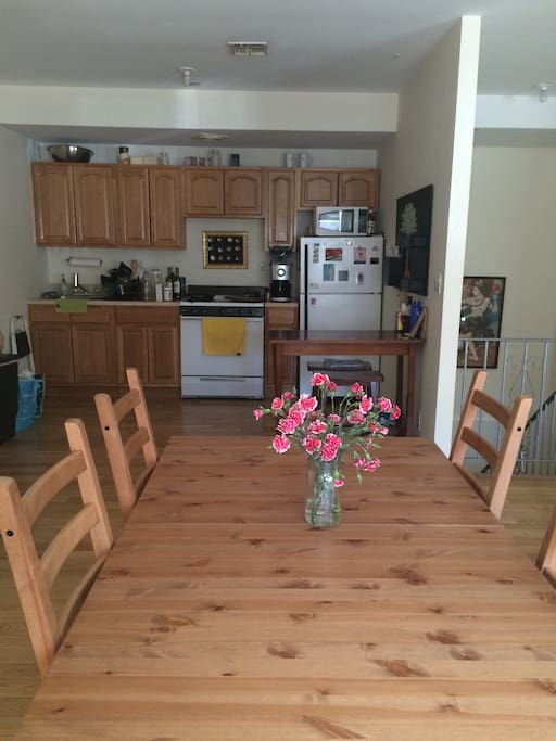 View from dining table into the kitchen. Includes fridge space, use of coffee machine, filtered water, stovetop and oven, small breakfast nook with two stools in the corner. (Stairs to bottom floor on the right.)