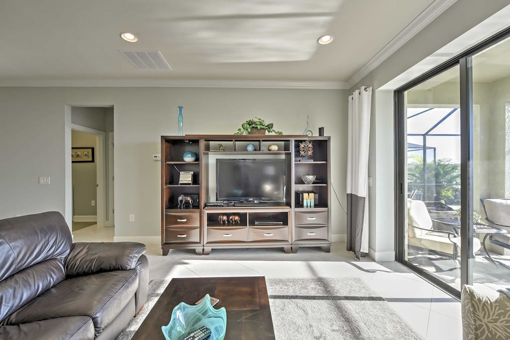 The living area includes a comfortable leather sofa, flat-screen Apple TV and sliding glass doors to access the backyard.