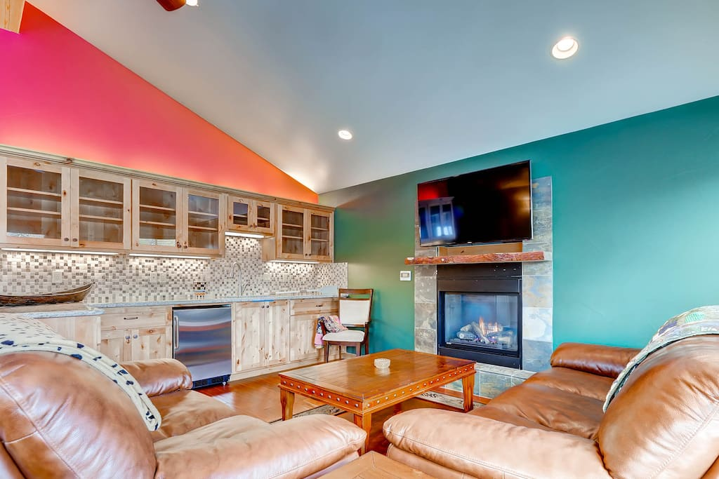 Upstairs living room with wet bar, fireplace, huge HDTV, and a game table