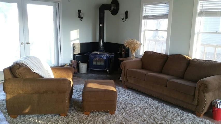 Main living room with fireplace and access to the back deck.
