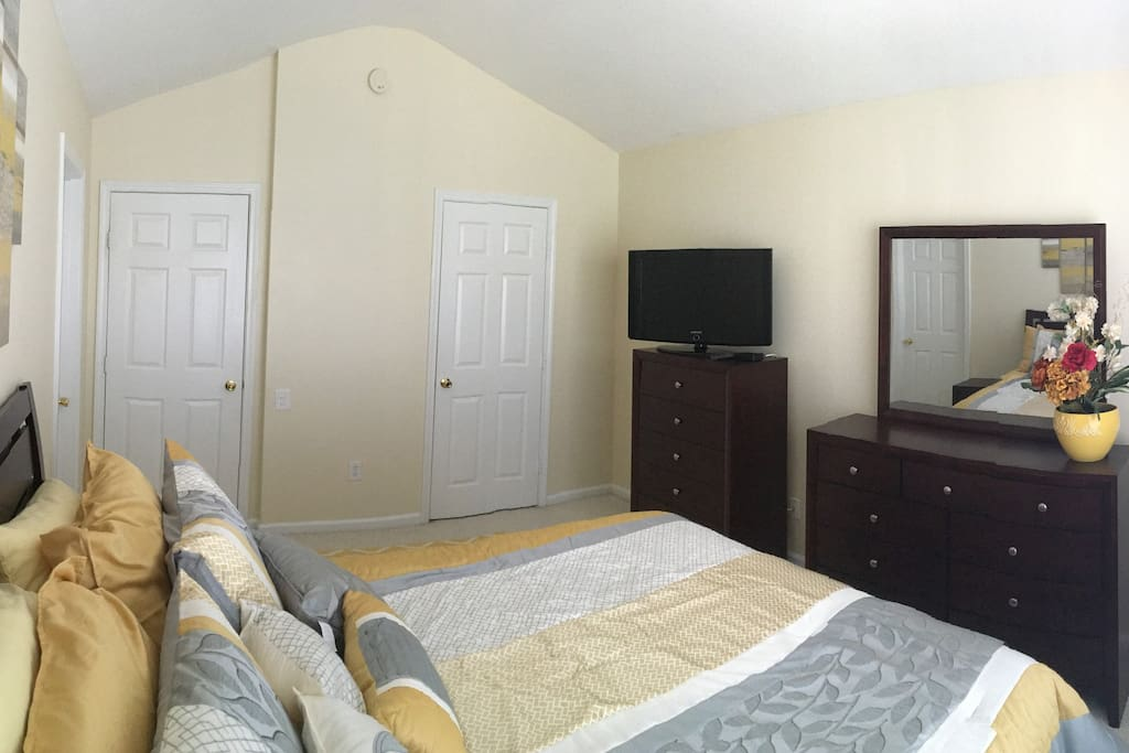 This is the guest bedroom. It includes a flatscreen television with cable, access to a shared bathroom, and a queen size bed.