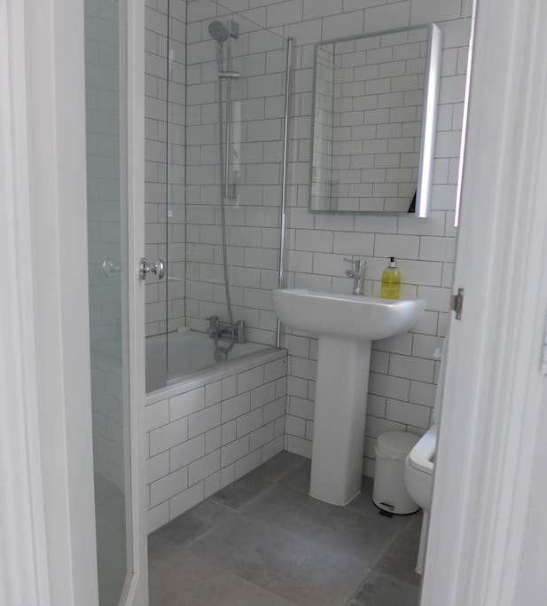 Fully tiled, new bathroom with shower and cabinet over sink which includes its own surround lighting for brightly lit shaving / make-up application!