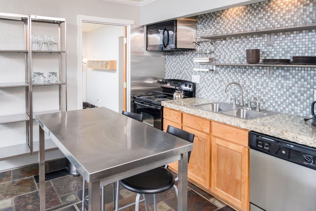 Granite kitchen with modern open shelving, center island seating, and a stainless steel French-door fridge.