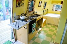 The kitchen is stocked with pots, pans, dishes, and utensils.  There's a gas stove and refrigerator, too.