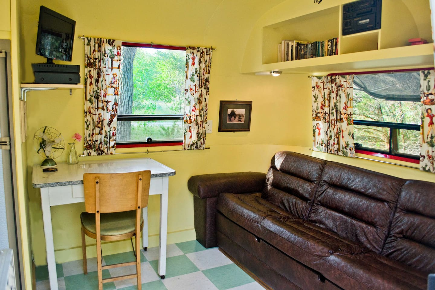 The living room has a full couch, table and chair, satellite tv, games, and books.