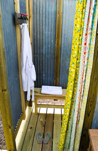 The outdoor shower has clothing hooks, a bench, and is big enough for two!