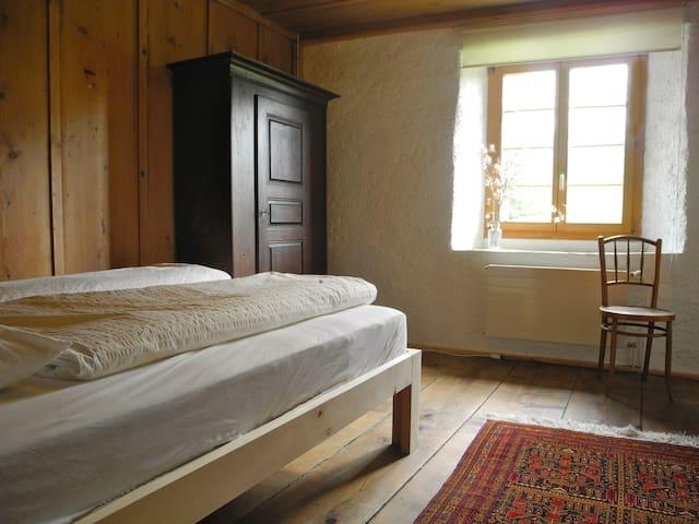 Schlafzimmer im ersten Stock mit einem Doppelbett, einem Schrank, einem Spiegel und Stühlen.
