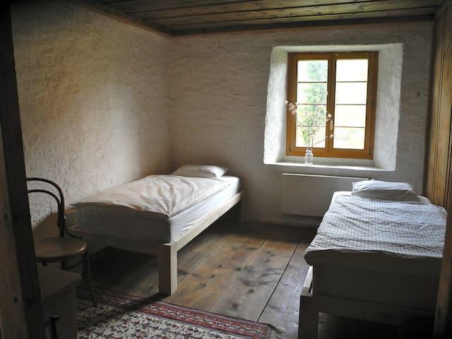 Schlafzimmer im ersten Stock mit zwei Einzelbetten, einer Kommode, einem Spiegel und einigen Stühlen. Alle Matratzen, Bettbezüge und Frottierwäsche im Haus sind neu.