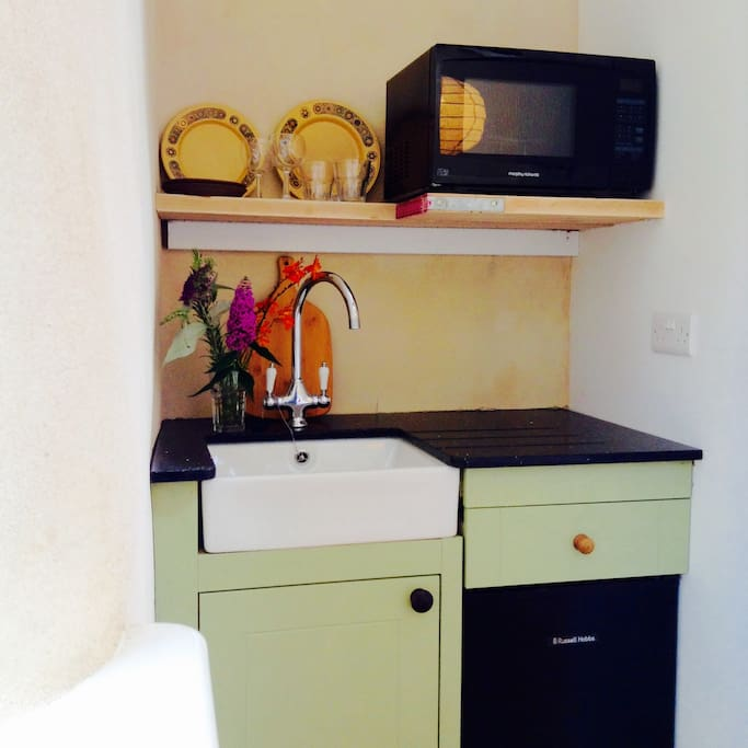 Mini kitchen with combination microwave oven and fridge, there's also a kettle and toaster.