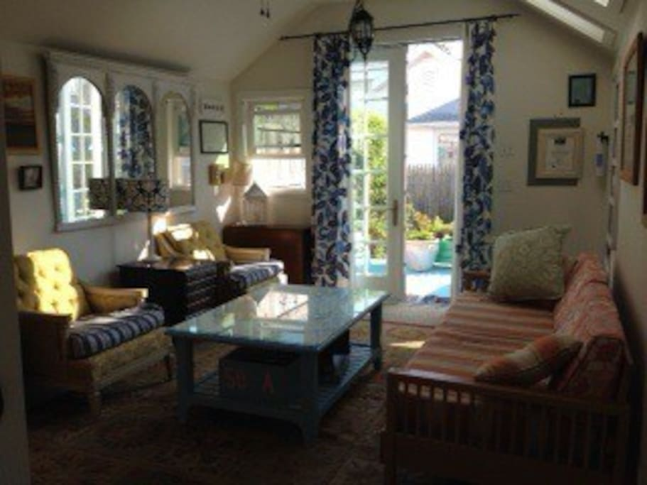 Living room has open feel due to high ceilings, skylights and french doors to deck