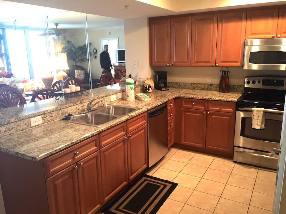 Large kitchen with stainless appliances and granite counters.