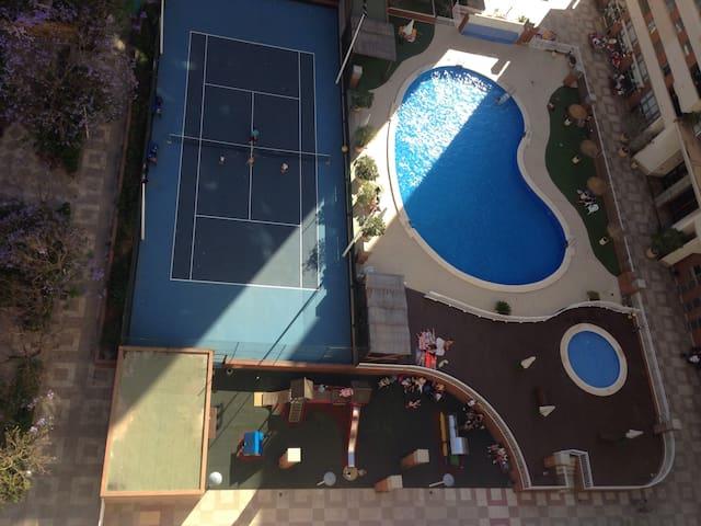 Hay piscina y pista de tenis