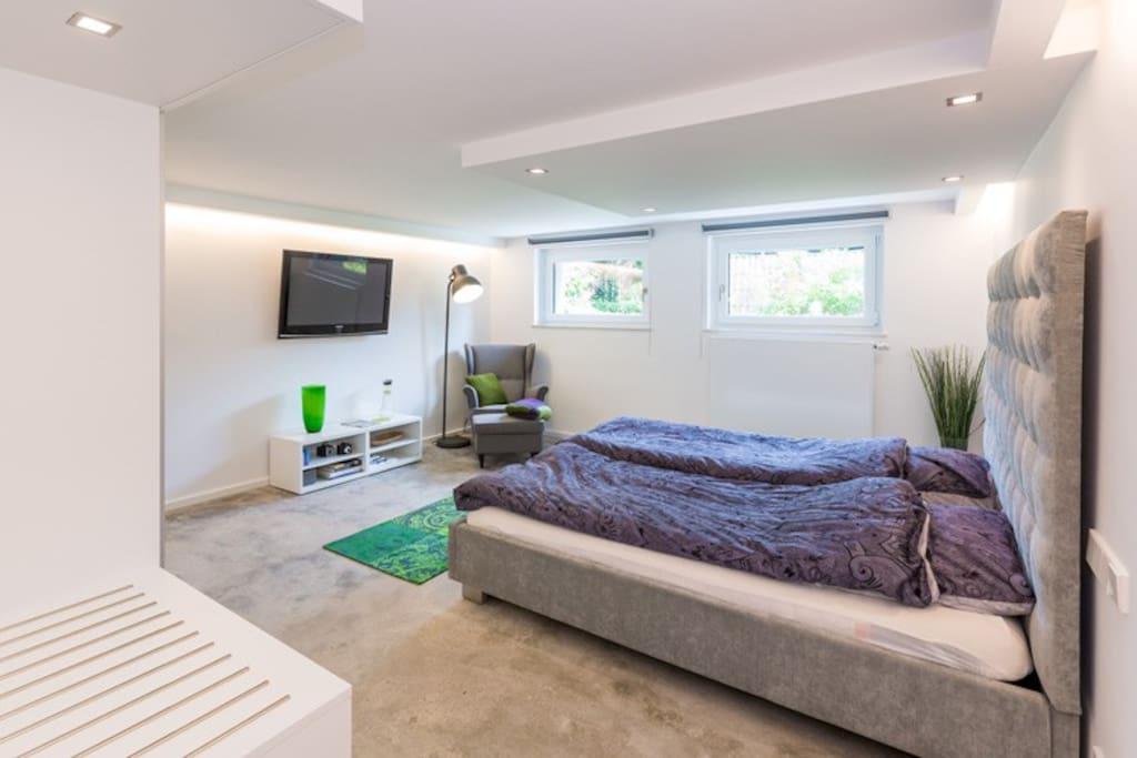 Angenehmer Wohnraum mit Flatscreen-TV und Lounge-Sessel