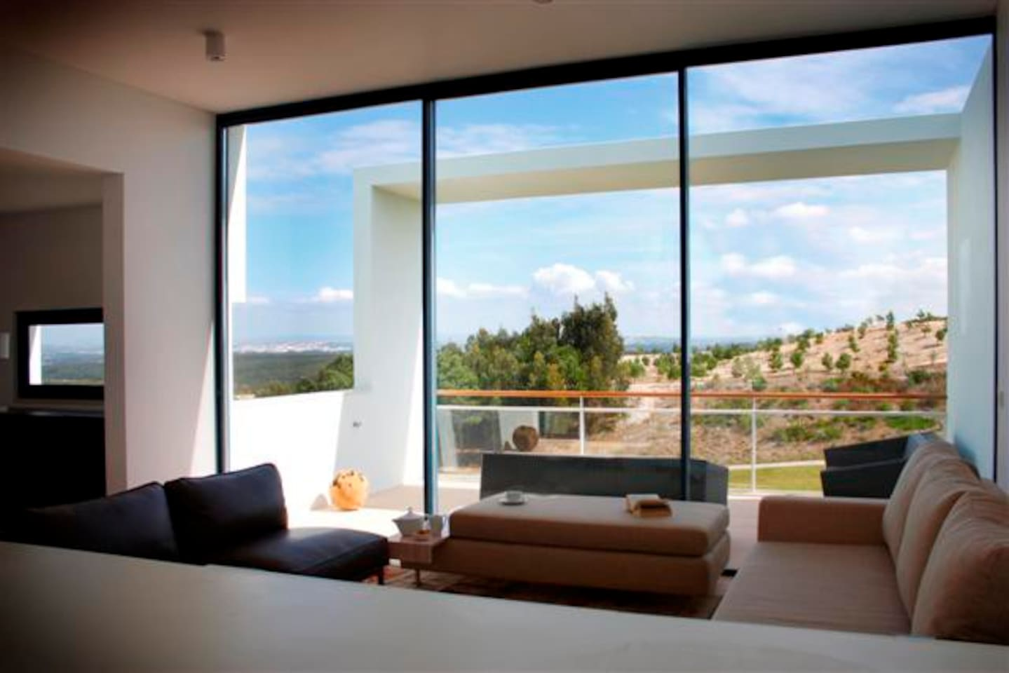 Living room leading to balcony and panoramic view of golf course and surrounding countryside.
