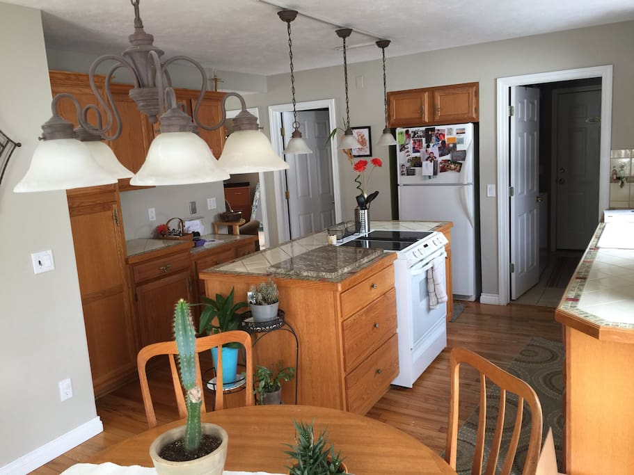Kitchen has custom tile countertops, island with downdraft oven/range and expandable teak table.