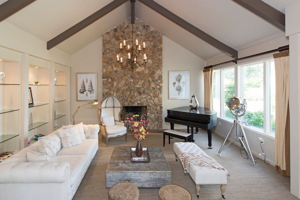 There's no shortage of elegance and style in the formal living room, featuring a wood-burning fireplace, grand piano and fabric sofa.