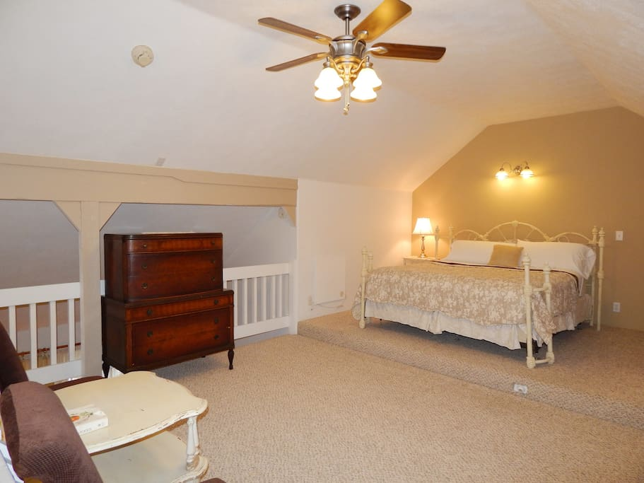 King bed in a spacious upstairs loft with vaulted ceiling and ceiling fan.