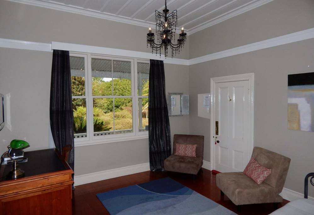 Spacious private lounge with seating, single bed, desk, TV/DVD, fridge, tea/coffee facilities