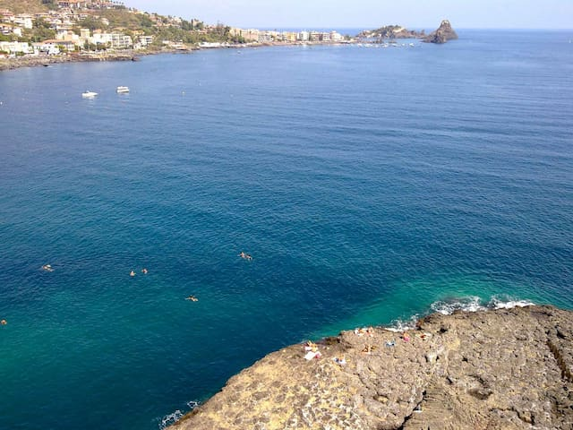 People swimming in the beautiful sea of Acicastello seen from the Normand Castle.