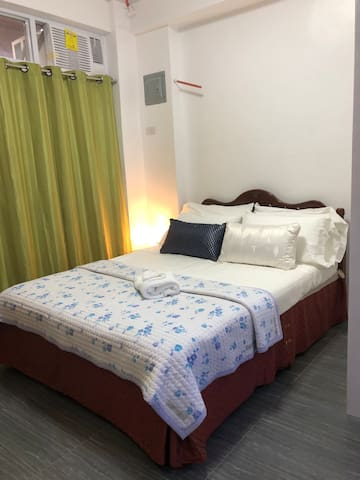 Bedroom with air-conditioning unit and a side table with touch lamp