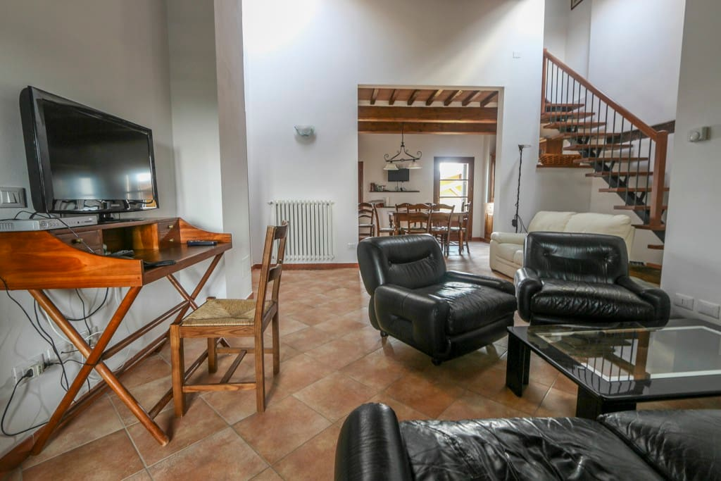 As you walk up the stairs, you arrive in this spacious sitting room, complete with comfortable leather sofas and chairs, coffee table, work area and TV screen.