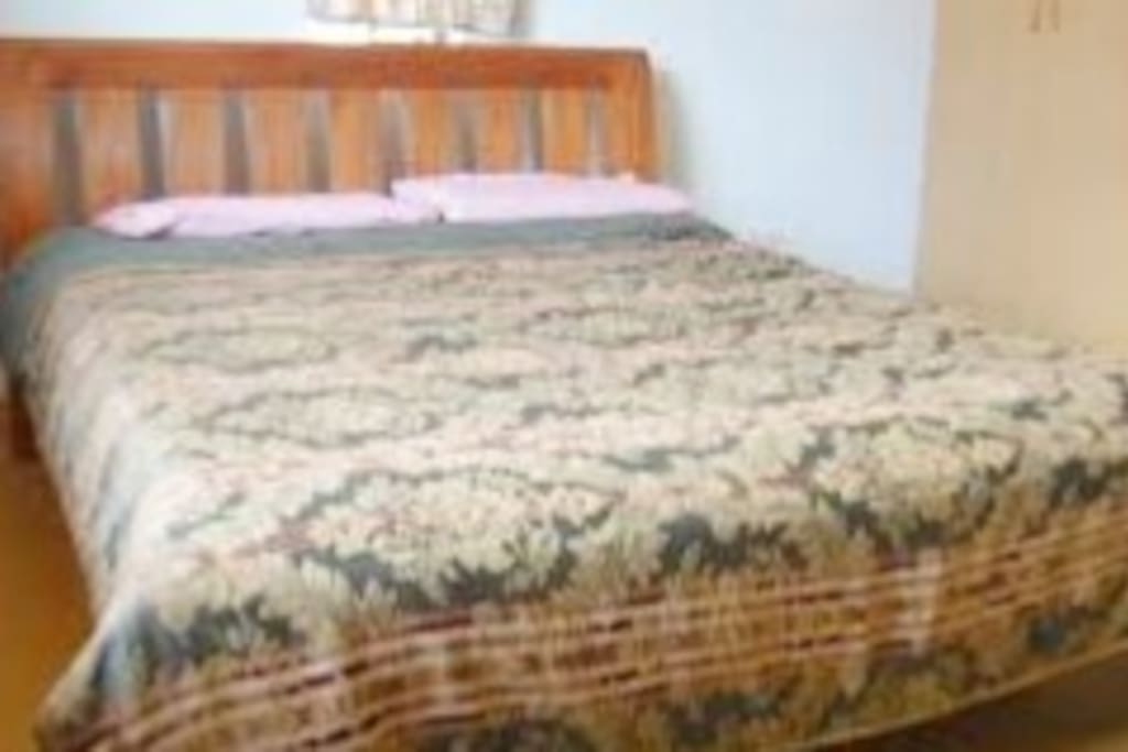 Spacious bedroom with brand new bedding and a TV and sideboard.
