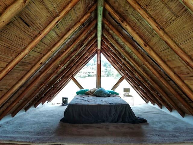 Alcoba en altillo, consta de una cama semi-doble con sus tendidos, mesa de noche, lampara, calefactor de ambiente y piso alfombrado.