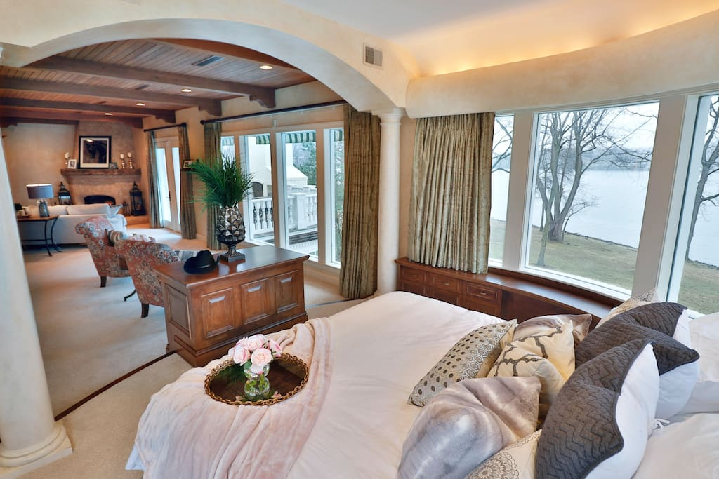 Bedroom 1 - Beautiful master suite features private living area, fireplace, king sized bed and balcony access. Floor-to-ceiling windows in the master bedroom allow natural light to flood the space and provides excellent lake views.