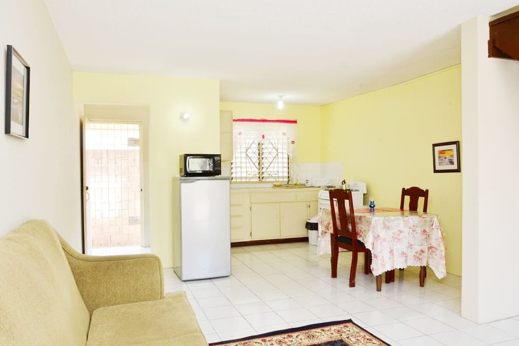 Fully equipped kitchen with utensils, full stove, fridge, microwave and dining area.