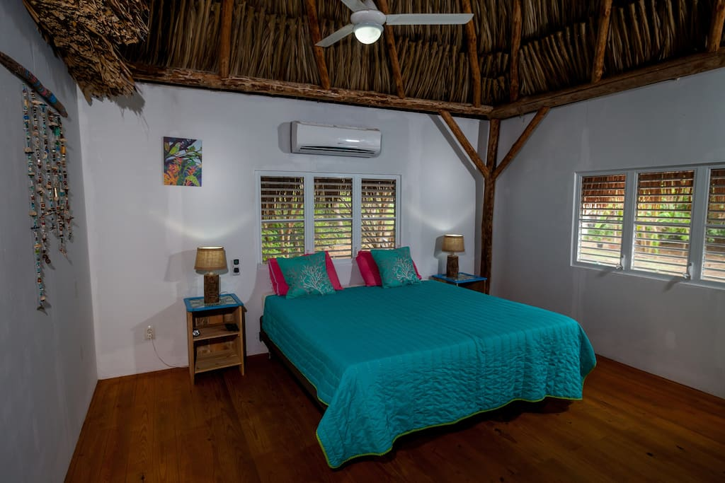 Bedroom 2, with two connected single beds, airconditioning, smart TV and mosquito nets.
