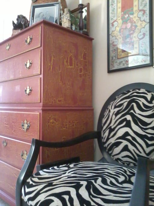 Antique Chinese embroidery panel above animal print chair.