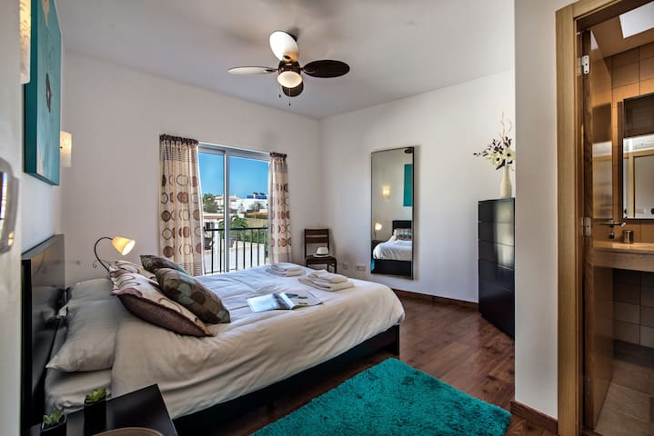 The master bedroom offers a large kingsize bed and air con