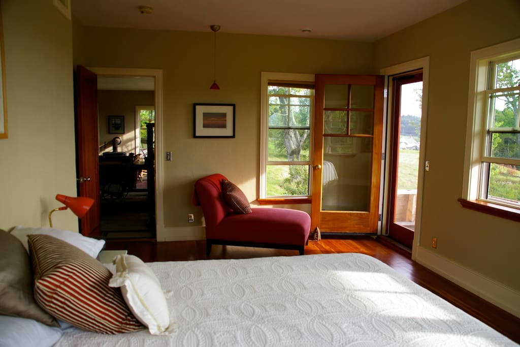 Airy bedroom with attached bath, screen door and porch.