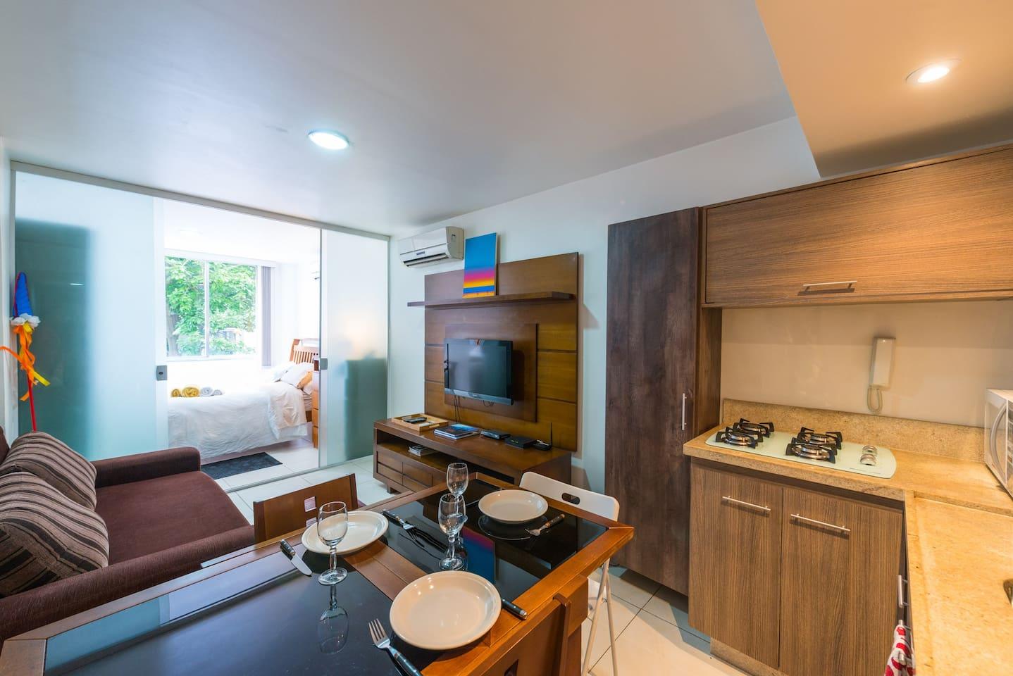 Visão geral do loft com o quarto ao fundo. Os ambientes são integrados e tudo está à mão.