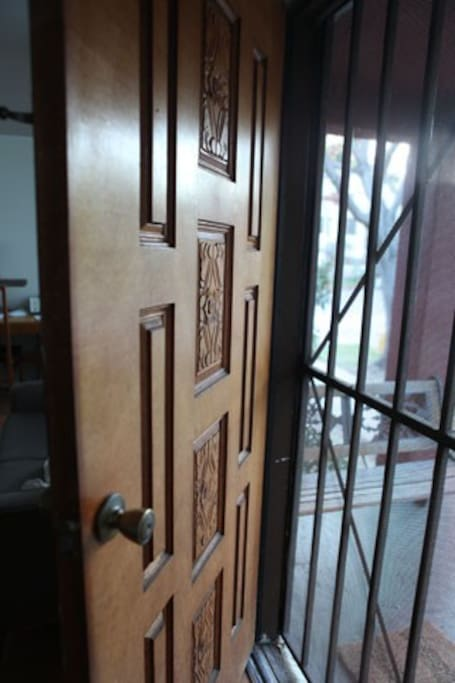 Carved solid wood door welcomes you in. The grill gate allows for privacy but breeziness when you leave the door open.
