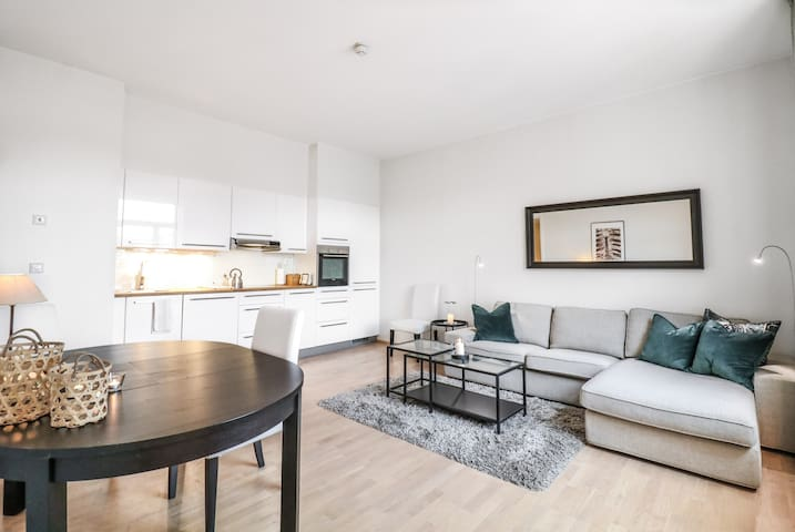 Spacious and well decorated  living room with dining area and an open kitchen gives the apartment a homey and bright feel