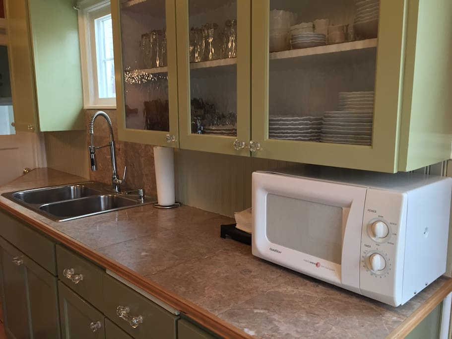 Dishes and glassware aplenty! A sink for washing up (no dishwasher) and a microwave