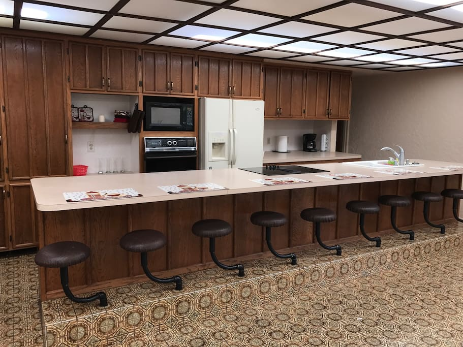 Huge kitchen with oversized eating bar that has 9 built-in stools.
