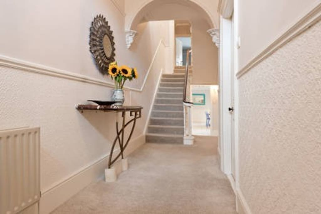 The hallway inside the front door of the house, two other guest bedrooms upstairs