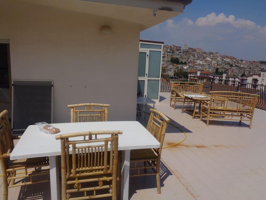 terrasse équipée de table, chaises, salon modulable et vue dégagée imprenable sur le village ancien de casteltermini