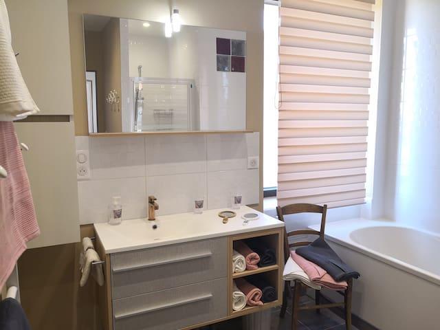 Salle de bains avec baignoire et douche spacieuse