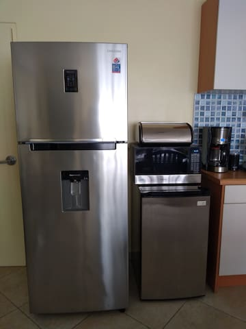 Two fridges, a microwave, and a coffee maker with a coffee beans grinder.