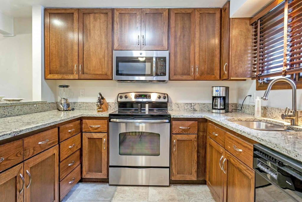 Fully equipped kitchen with stainless appliances and granite countertops, open to living and dining.