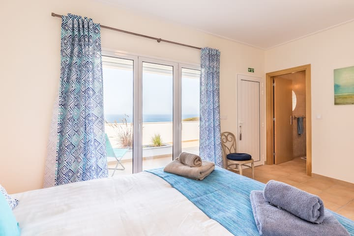 Master bedroom with a view. Double doors to downstairs balcony (one of two) with a view. The perfect spot for coffee in bed or in the sun!